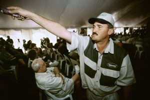 A guy is helping the auctioneer to detect bidders in the crowded auction-tent.