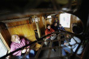 "Passengers enjoy the historic-train journey, in the former ""wood class"" (3rd class) of the Deutsche Reichsbahn."