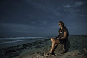 A volunteer sits on a beach at night to protect incoming turtles from poachers.